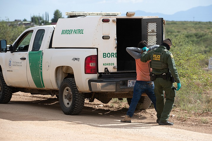 """A Border Patrol agent with a migrant who was caught near Naco in August 2020. Customs and Border Protection recorded almost 1.1 million border """"encounters"""" in the first nine months of fiscal 2021, a potentially record-setting pace, but advocates there may be double-counting in those numbers. (Jerry Glaser/U.S. Customs and Border Protection via Cronkite News)"""