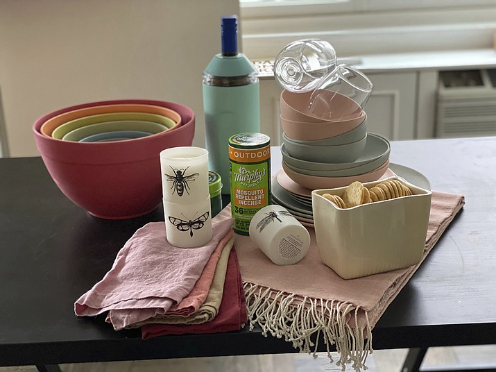 This image provided by Katie Workman shows colorful bamboo plates and bowls, stylish acrylic wine glasses, a sleek wine chiller, a cozy throw for cooler nights, and smart bug-repelling gear. These are just a few ways you can amp up your outdoor entertaining this summer. (Katie Workman via AP)