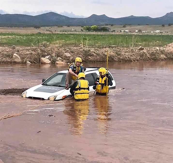 A Central Arizona Fire and Medical Authority technical rescue team helps a man from his car in a flooded area near Paulden on Friday, July 23, 2021. (CAFMA/Courtesy)