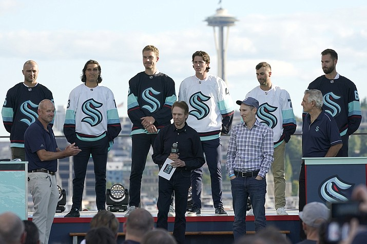 New Seattle Kraken NHL hockey players, back row from left, Mark Giordano, Brandon Tanev, Jamie Oleksiak, Hadyn Fluery, Jordan Eberle and Chris Dreidger stand on stage with Kraken owners David Wright, front left, Jerry Bruckheimer, front center, and Andy Jassy, front second from right, and Kraken general manager Ron Francis, front right, Wednesday, July 21, 2021, after being introduced during the Kraken's expansion draft event in Seattle. Jassy is also president and CEO of Amazon.com. (Ted S. Warren/AP)