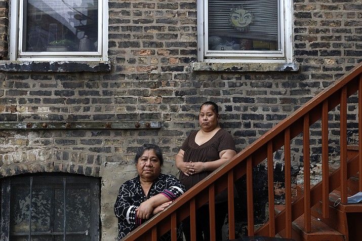 Maria Elena Estamilla, 62, left and her daughter Esmeralda Triquiz pose for a photo June 30, 2021, in Chicago's Pilsen neighborhood. Estamilla's last full medical exam was in 2015 and she sees no options for care as a Mexican immigrant without legal permission to live in the U.S. She's not eligible for Medicare, Medicaid or Affordable Care Act coverage. As a child care worker, she didn't have employer coverage. She can't afford private insurance. (Shafkat Anowar/AP)