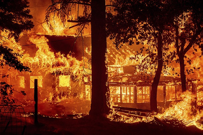 Flames from the Dixie Fire consume a home in the Indian Falls community of Plumas County, Calif., Saturday, July 24, 2021. The fire destroyed multiple residences as it tore through the area. (Noah Berger/AP)