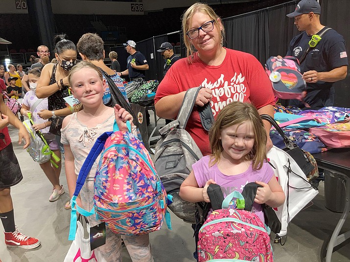 Chino Valley mother Amanda Brown with her daughters, Bayleigh, 8, left, and Ashalen, 6, at the first-ever Yavapai County Back to School Health and Wellness Fair at the Findlay Toyota Center in Prescott Valley, Tuesday, July 27, 2021. Amanda also selected a camouflage backpack for the girls' older brother. (Nanci Hutson/Courier)