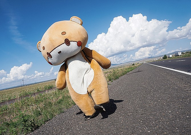 """Jessy Larios of California dons his bear costume, which he refers to as """"Bearsun,"""" while walking east on Interstate 40 near Ash Fork on Tuesday, July 27, 2021. This year, Larios has garnered a significant social media following by starting his own campaign that has him walking from Los Angeles to New York City in his costume to raise money for charity. (Aaron Valdez/Courier)"""