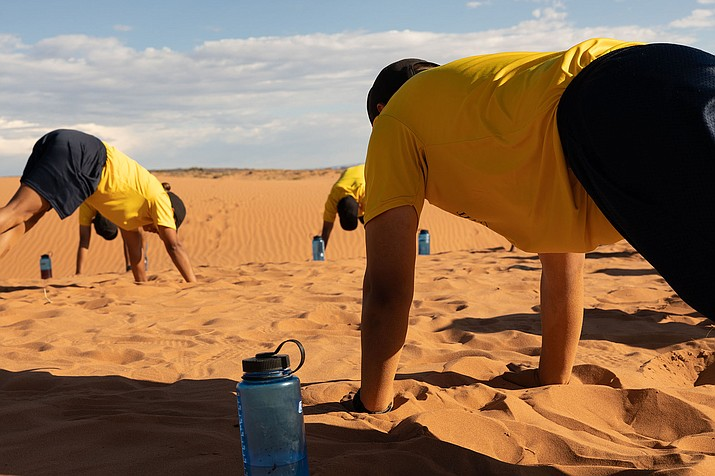 Navajo Nation Police recruits stretch after running on sand dunes for physical training in Chinle, Arizona, on the reservation. A recent report said the 200-member department needs hundreds more officers to do its job. (Beth Wallis/News 21)