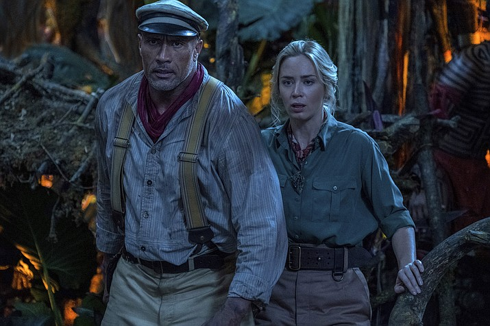 """This image released by Disney shows Emily Blunt, right, and Dwayne Johnson in a scene from """"Jungle Cruise."""" (Disney via AP)"""