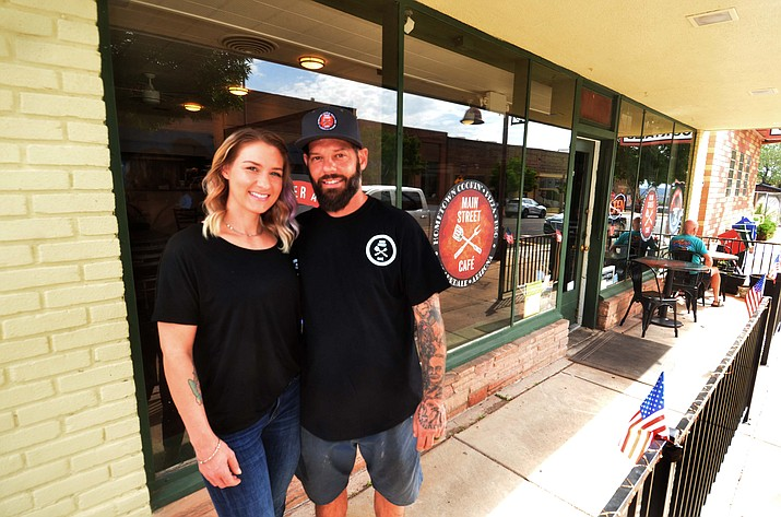 Scott and Chelsea Honey take a moment to pose in front of the Main Street Café in Clarkdale. (Vyto Starinskas/Independent)