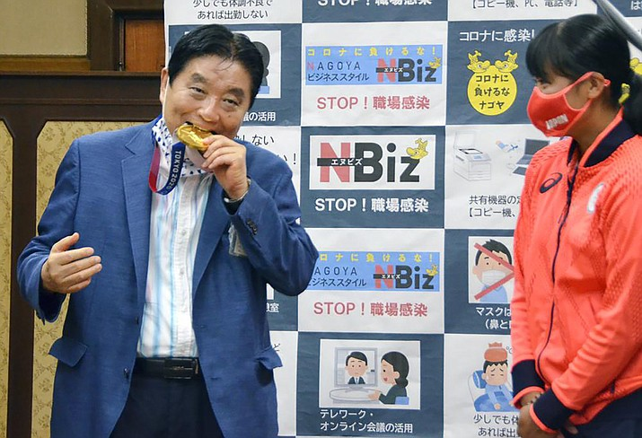 Nagoya Mayor Takashi Kawamura, left, bites the Olympic gold medal of Miu Goto, right, of Japan softball team who won the event at the 2020 Summer Olympics, at the city office building in Nagoya, central Japan, Wednesday, Aug. 4, 2021. (Kyodo News via AP)