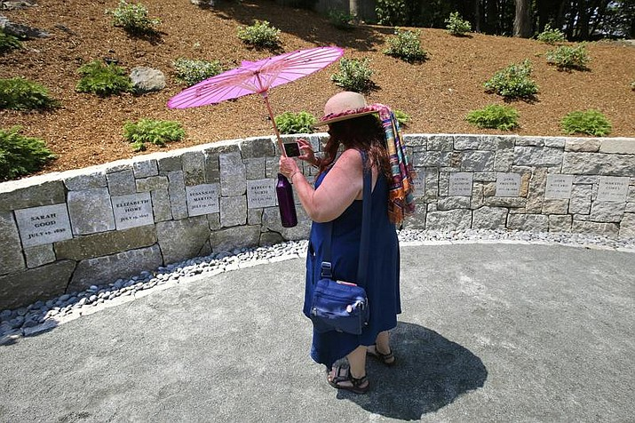 In this July 19, 2017 photo, Karla Hailer, a fifth-grade teacher from Scituate, Mass., shoots a video where a memorial stands at the site in Salem, Mass., where five women were hanged as witches more than 325 years earlier. A woman convicted of witchcraft in 1693 and sentenced to death at the height of the Salem Witch Trials finally will be exonerated if Massachusetts lawmakers approve a bill inspired by a curious eighth-grade history class. (Stephan Savoia/AP, File)