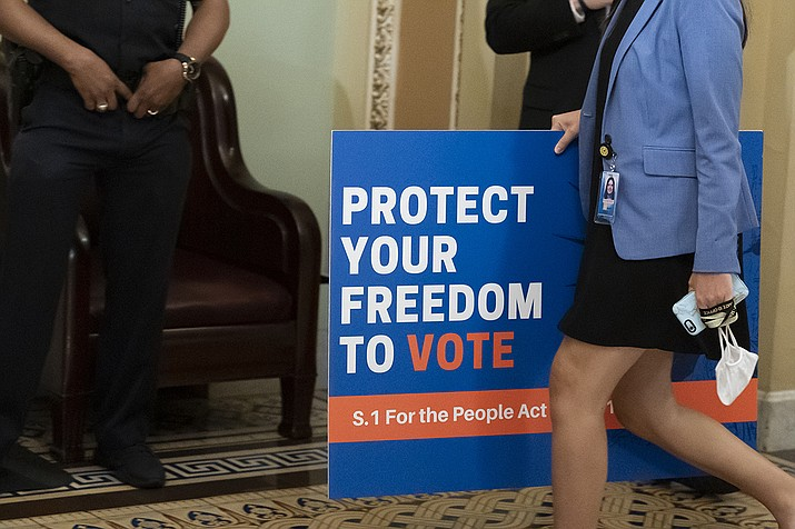 In this June 22, 2021, file photo, an aide carries a sign to the Senate floor before test vote on the For the People Act, a sweeping bill that would overhaul the election system and voting rights, at the Capitol in Washington. Both parties are bracing for a major legal fight over redistricting. Democrats need court wins more than Republicans because they control the redrawing of political maps in far fewer states than the GOP. (Alex Brandon, AP File)