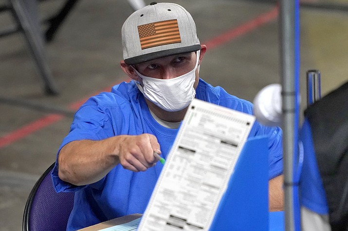 In this May 6, 2021, file photo, Maricopa County ballots cast in the 2020 general election are examined and recounted by contractors working for Cyber Ninjas at Veterans Memorial Coliseum in Phoenix. Maricopa County officials are sending a bill for $2.8 million to the state Senate to cover the cost of having to acquire new voting machines. (Matt York/AP, file)