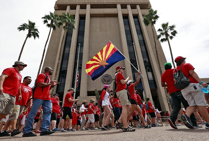 In this 2018 file photo, teachers rally outside of Arizona Gov. Doug Ducey's Executive Tower in Phoenix on their third day of walkouts. The Arizona Supreme Court on Thursday, Aug. 19, 2021, ruled the income tax surcharge on the wealthy can remain, at least for the time being. But it may be legally impossible to actually get any of those dollars into the classroom, which was the intent of the sponsors of Proposition 208. (Matt York/AP, file)