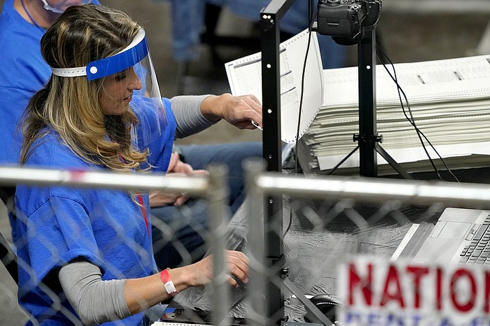 In this May 6, 2021, file photo, Maricopa County ballots cast in the 2020 general election are examined and recounted by contractors working for Florida-based company, Cyber Ninjas, at Veterans Memorial Coliseum in Phoenix. Supporters of former President Donald Trump who were hired to review the 2020 vote count in Arizona's largest county are preparing to deliver their report to state Republicans on Monday, though their findings won't immediately be made public. (Matt York/AP, file)
