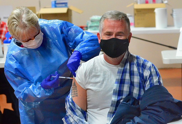 This undated file photo shows a patient receiving the COVID-19 vaccine by a Spectrum Healthcare nurse. Private businesses in Arizona are free to require that their workers be vaccinated against COVID-19, Attorney General Mark Brnovich has concluded. And Brnovich said companies have right to make the same demand of customers. (Vyto Starinskas/Independent, file)