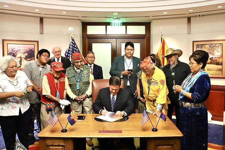 Arizona Gov. Doug Ducey (center) signs SB 1802 officially recognizing Aug. 14 as National Navajo Code Talker Day. (Photo/Office of the Navajo President and Vice President)