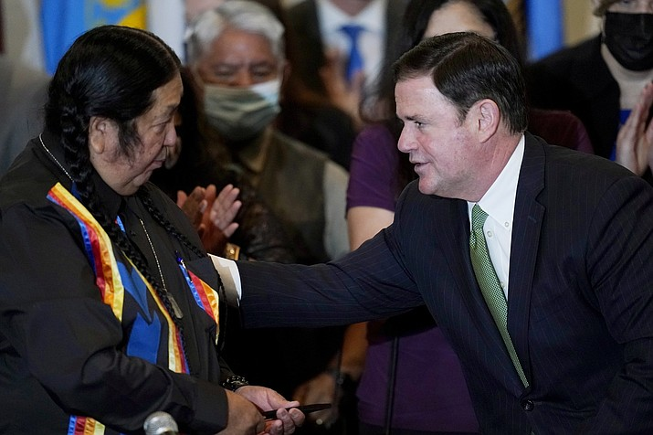 Gov. Doug Ducey, right, talks with Dr. Damon R. Clarke, left, Chairman of the Hualapai Tribe, after a bill signing allowing a major expansion of sports betting in Arizona at an event at the Heard Museum on April 15, 2021, in Phoenix. Now, the Yavapai-Prescott Indian Tribe is suing to halt the progress. (Ross D. Franklin/AP, file)