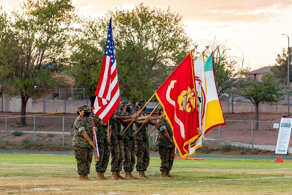"""Tuba City High School JROTC presenting the """"colors"""" prior to kickoff. Flags included: Hopi Tribe, Navajo Nation, U.S. Marine Corps and the flag of the United States. Several Warrior players with an interception which eventually led to a touchdown. (Gilbert Honanie/NHO)"""