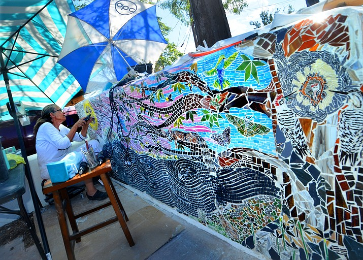 Rebecca Murray uses a Dremel tool to finish the Yavapai-Apache sun on her stained-glass bench mural Wednesday, Aug. 25, 2021, in Camp Verde. (Vyto Starinskas/Independent)