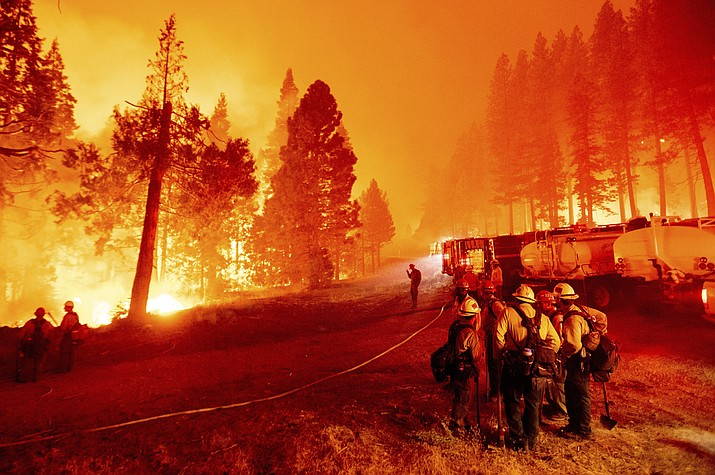 In this Thursday, Aug. 26, 2021 file photo, the Caldor Fire burns along both sides of Highway 50 as firefighters work to stop its eastward spread in Eldorado National Forest, Calif. Last week, managers overseeing the fight against the massive wildfire scorching California's Lake Tahoe region thought they could have it contained by the start of this week. Instead, on Monday, Aug. 30, 2021, the Caldor Fire crested the Sierra Nevada, forcing the unprecedented evacuation of all 22,000 residents of South Lake Tahoe. (AP Photo/Noah Berger, File)
