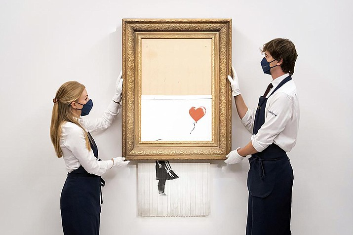 """Art handlers at Sotheby's auction house hold Banksy's """"Love is in the Bin,"""" before it returns to auction at Sotheby's, London, Friday, Sept. 3, 2021. A Banksy artwork that was sensationally shredded just after it sold for $1.4 million us up for sale again - at several times the price. Sotheby's said Friday that """"Love is in the Bin"""" will be offered at an Oct. 14 auction in London, with a pre-sale estimate of 4 million pounds to 6 million pounds ($5.5 million to $8.3 million). (Dominic Lipinski/PA via AP)"""