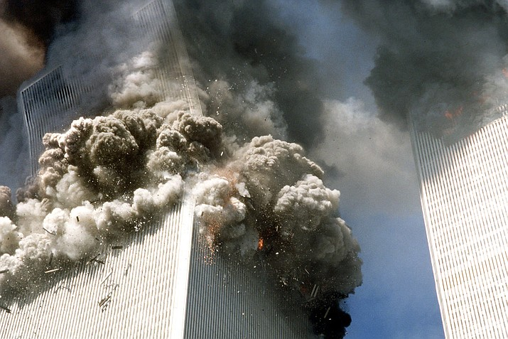 The south tower of the World Trade Center, left, begins to collapse after a terrorist attack in New York, Sept. 11, 2001. (AP Photo/Gulnara Samoilova)
