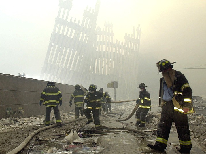 With the skeleton of the World Trade Center twin towers in the background, New York City firefighters work amid debris after the terrorist attacks of Sept. 11, 2001. (AP Photo/Mark Lennihan)