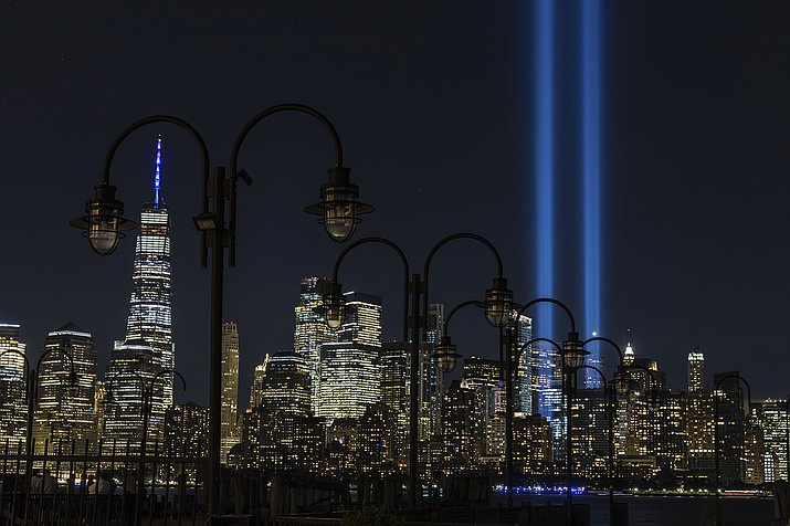 Tribute in Light, two vertical columns of light representing the fallen towers of the World Trade Center shine against the lower Manhattan skyline seen from Jersey City, N.J., Friday, Sept. 11, 2020. (AP Photo/Stefan Jeremiah))