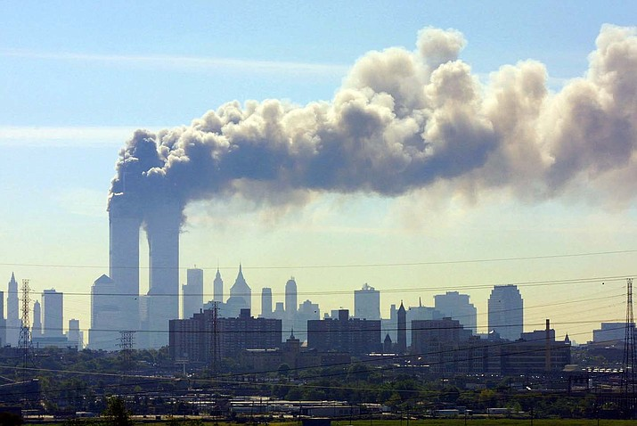 In this Sept. 11, 2001, file photo, as seen from the New Jersey Turnpike near Kearny, N.J., smoke billows from the twin towers of the World Trade Center in New York after airplanes crashed into both towers. (Gene Boyars/AP, file)