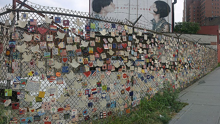 A small monument to the victims of the Sept. 11, 2001 terrorist attacks in the United States is shown on the fence of a car lot on Greenwich and Seventh avenues in New York City in 2004. (Photo by DAVID ILIFF, cc-by-sa-2.5, https://bit.ly/3BRgxwA)
