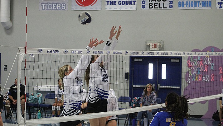 Victoria Chapman, left, and Morgan Garrison, right, of Kingman Academy High School, attempt a block during the Lady Tigers 3-0 win over rival Kingman High School in a girls volleyball game played on Tuesday, Sept. 7. (Photo by Casey Jones/Kingman Miner)