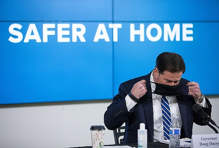 Arizona Gov. Doug Ducey puts on his face mask during a news conference about the coronavirus, Thursday, July 16, 2020, in Phoenix. (Cheryl Evan/The Arizona Republic via AP, Pool)