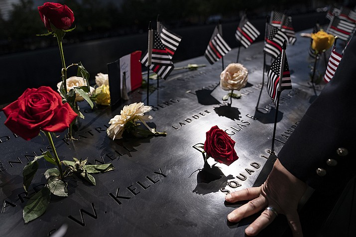 A firefighter places his hand on the name engravings on the south pool during ceremonies to commemorate the 20th anniversary of the Sept. 11 terrorist attacks, Saturday, Sept. 11, 2021, at the National September 11 Memorial & Museum in New York. (John Minchillo/AP)