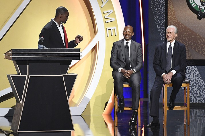 Inductee Chris Bosh holds up a ring to give to Pat Riley, right, as Ray Allen looks on during the 2021 Basketball Hall of Fame Enshrinement ceremony, Saturday, Sept. 11, 2021, in Springfield, Mass. (Jessica Hill/AP)