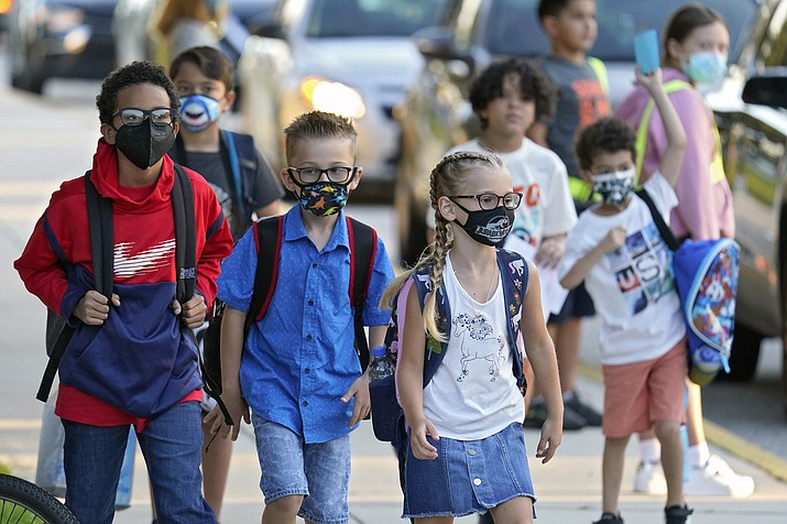 In this Aug. 10, 2021, file photo, students, some wearing protective masks, arrive for the first day of school in Riverview, Florida. The Arizona attorney for a coalition of educators, school board members, child welfare advocates and others warned a judge Monday, Sept. 13, that children could die if she does not void a legislative ban on schools requiring students to be masked. (Chris O'Meara/AP, file)