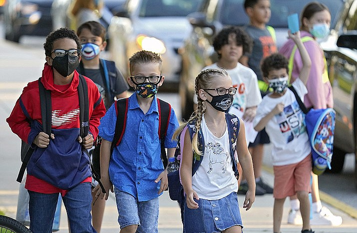 In this Aug. 10, 2021 photo, students - some wearing protective masks - arrive for the first day of school. The Arizona attorney for a coalition of educators, school board members, child welfare advocates and others warned a judge Monday, Sept. 13, that children could die if she does not void a legislative ban on schools requiring students to be masked. (Chris O'Meara/AP, file)
