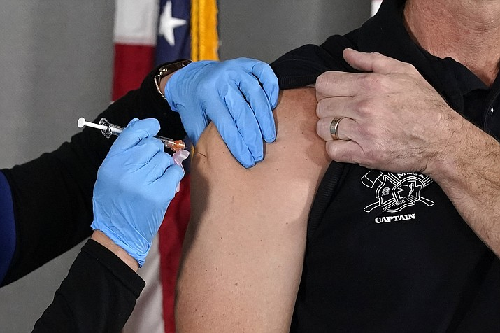 In this Dec. 16, 2020, file photo, the Pfizer vaccine for COVID-19 is administered at the Arizona Department of Health Services State Laboratory in Phoenix. Arizona attorneys who specialize in labor law say the decision by President Joe Biden that large employers must have all workers vaccinated is well within the power of the federal government. (Ross D. Franklin/AP, file)