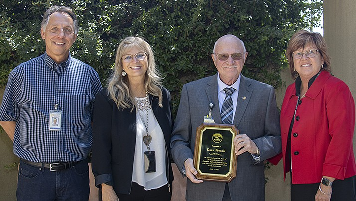 Kingman Healthcare Inc. board officers Jim Baker, Coral Loyd and Krystal Burge present David French, second from right, with a plaque to honor his decades of service on the board. (Courtesy photo)