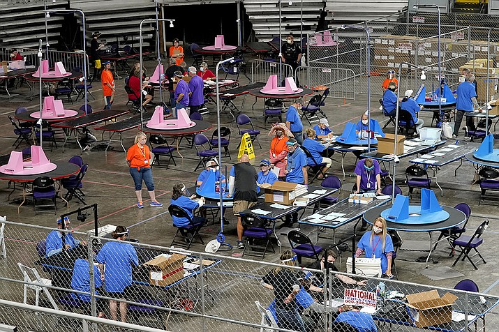 In this May 6, 2021, file photo, Maricopa County ballots cast in the 2020 general election are examined and recounted by contractors working for Florida-based company, Cyber Ninjas at Veterans Memorial Coliseum in Phoenix. The Arizona Supreme Court upheld an appeals court ruling on Tuesday, ruling that that the records of Cyber Ninjas, as related to the audit, are public. (Matt York, Pool, AP File)