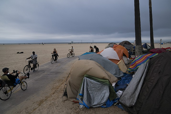 In this June 29, 2021, photo people ride their bikes past a homeless encampment set up along the boardwalk in the Venice neighborhood of Los Angeles. The share of Americans living in poverty rose slightly as the COVID pandemic shook the economy last year, but massive relief payments pumped out by Congress eased hardship for many, the Census Bureau reported Tuesday, Sept. 14. The official poverty measure showed an increase of 1 percentage point in 2020, indicating that 11.4% of Americans were living in poverty. It was the first increase in poverty after five consecutive annual declines. (Jae C. Hong/AP, File)