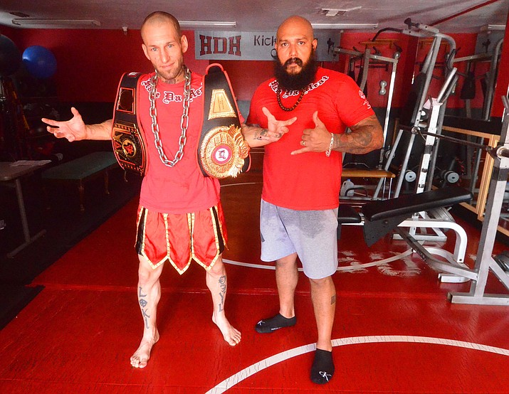 Loki Legionson, left, and Robert Gonzales take a break during a workout on Thursday, Sept. 9, 2021, at the HDH Powerhouse Gym in Cottonwood. Legionson is holding his Arizona Rage In the Cage Muay ThaiState Title belt and his 2016 Muay Thai Alliance World Championship belt. (Vyto Starinskas/Independent)