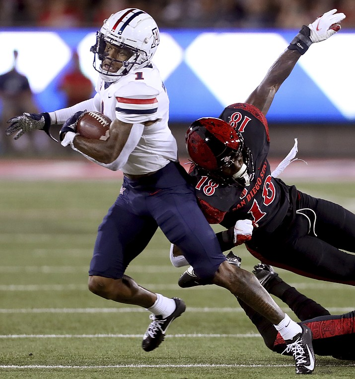 Arizona receiver Stanley Berryhill III bounces off San Diego State safety Trenton Thompson (18) after his catch and heads for the end zone for a touchdown during the first half of an NCAA game Saturday, Sept. 11, 2021, in Tucson. (Kelly Presnell/Arizona Daily Star via AP)
