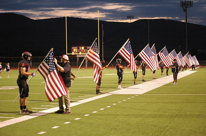 Members of the Bradshaw Mountain High School football team hoist American flags to honor the 13 serviceman killed in Afghanistan, before Friday night's game against Cactus. (Doug Cook/Courier)