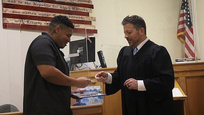 Kingman Municipal Court Judge Jeffrey Singer, right, presents U.S. Army veteran Joshua Gray with his graduation certificate from Kingman Veterans Treatment Court. (Photo by Travis Rains/Kingman Miner)