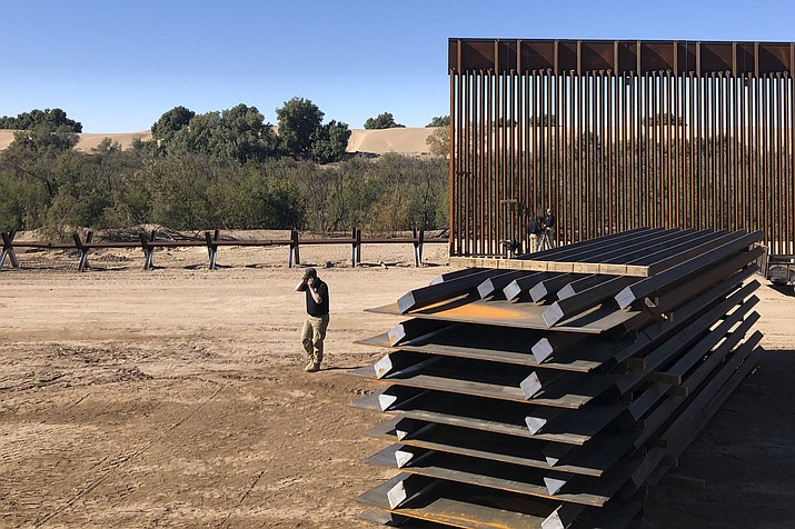In this January 2020 file photo, a man passes new border wall sections, right, as they replace the old fencing, left, near Yuma, Arizona. Tyler Alexander, a trial attorney with the agency's natural resources section, told Judge Dominic Lanza there are a host of reasons why Arizona cannot sue over the decision by the Biden administration to halt further wall construction, including unfinished projects in the state. (Elliot Spagat/AP, file)