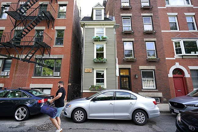 In this Aug. 13, 2021 photo, a man walks by Boston's famous Skinny House, at center, after it was listed for sale for $1.2 million. The sale of the home was closed last week for $1.25 million, according to Zillow. (Elise Amendola/AP, File)