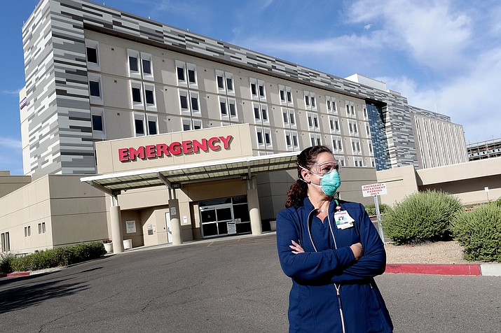 A nurse stands outside a hospital at the end of her overnight shift early in 2020 in Scottsdale, Arizona. The State Board of Nursing is slow in handling complaints, according to a new state report, a practice it says that could endanger public safety. (Matt York/AP, file)