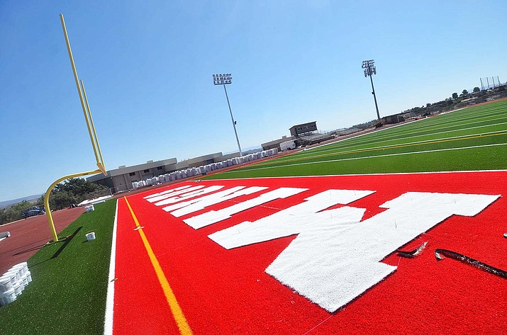 New letters and red synthetic grass are put down on the field Wednesday, Sept. 22, 2021. Mingus Athletic Director Yancey DeVore said he hopes the school will have its first home game Friday, Oct. 8, when the synthetic field should be complete. (Vyto Starinskas/Independent)