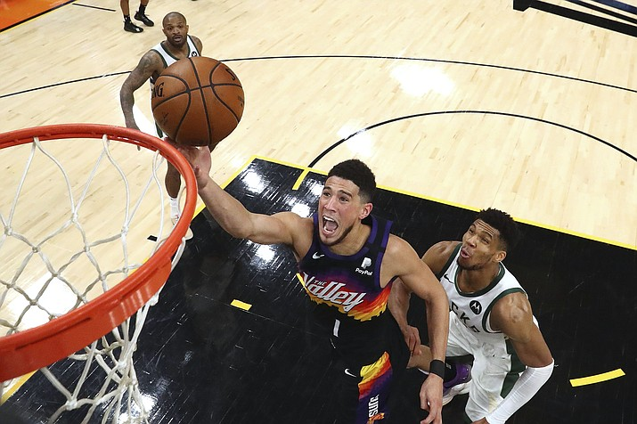 In this Saturday, July 17, 2021, photo, Phoenix Suns guard Devin Booker (1) shoots past Milwaukee Bucks forward Giannis Antetokounmpo, right, during the second half of Game 5 of the NBA Finals, in Phoenix. On Sunday, Sept. 26, 2021, the Suns announced that Booker will miss the start of training camp after being placed in the league's health and safety protocol. (Mark J. Rebilas/Pool Photo via AP, File)