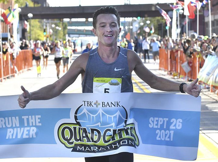 Tyler Pence of Springfield, Ill., finishes first in the TBK Bank Quad Cities Marathon on Sunday, Sept. 26, 2021, in Moline, Ill. The Illinois man unexpectedly won the marathon when the two Kenyan runners who had far outpaced him were disqualified after being diverted off the course by a race volunteer bicyclist. (Gary L. Krambeck/Quad City Times via AP)