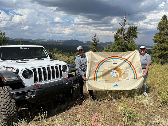 Racquel Black and Shandinna Nizhoni Peters hold up the Navajo Nation flag as they prepare for the Rebelle Rally, an all-women endurance and navigation competition. (Photo courtesy Asdzaa Skoden Rebelles)